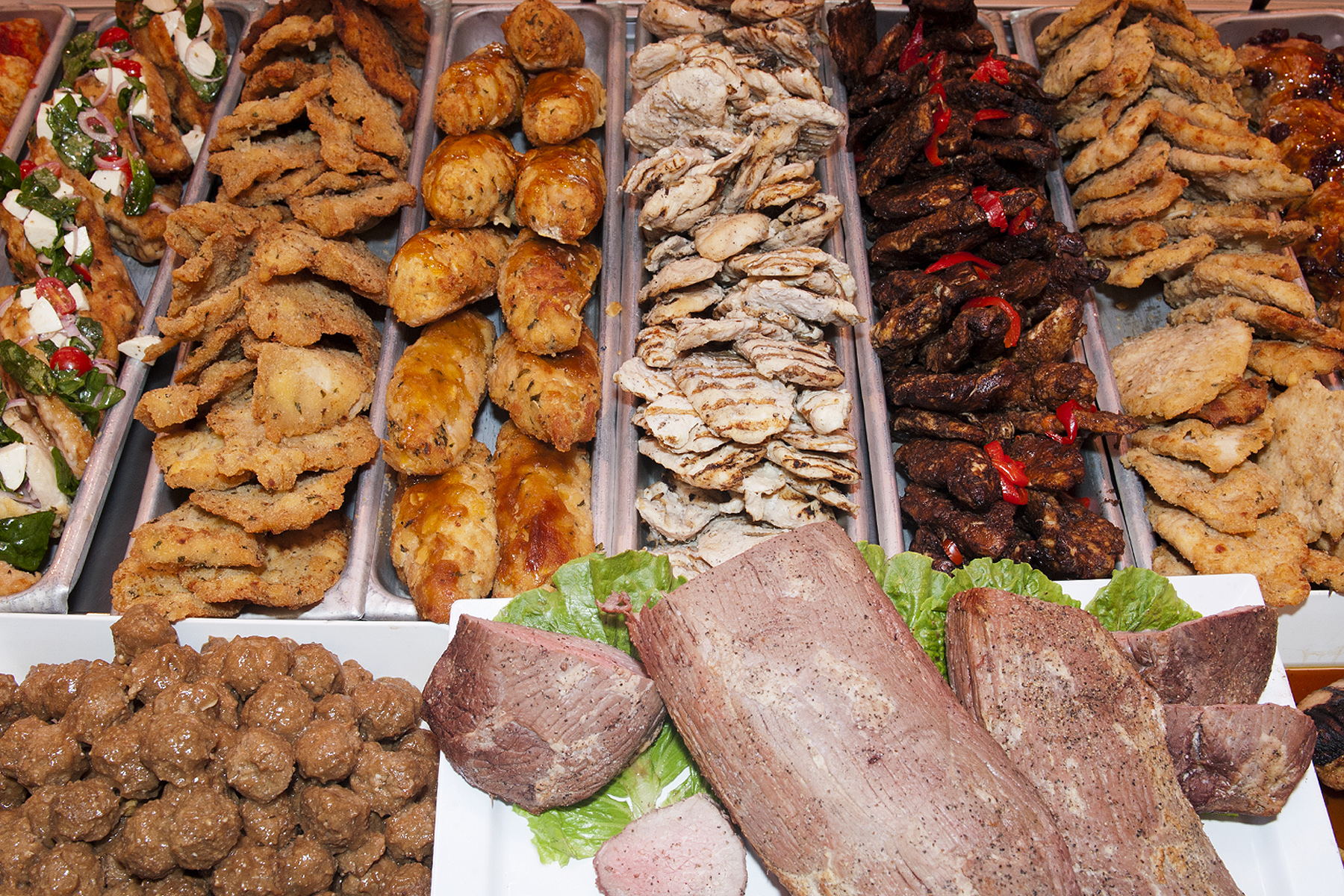 chicken cutlets, meatballs, grilled chicken, and other kinds of meat in a deli case