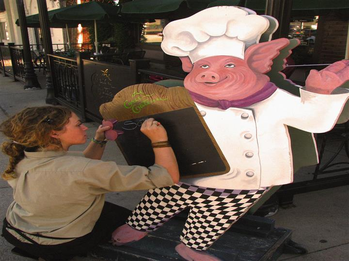 Cut out of a chef pig with a Women writing on it
