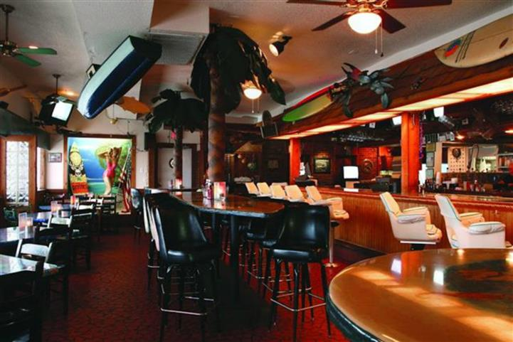 Photo of interior of establishment with bar, tables, and fans