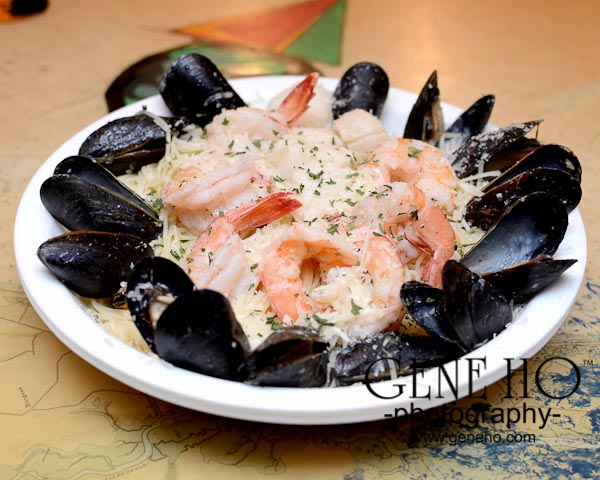 Mussels and shrimp over pasta in shallow white bowl
