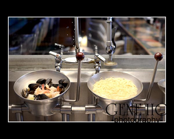Shrimp and mussels in metal bowl alongside linguini in separate metal bowl in kitchen