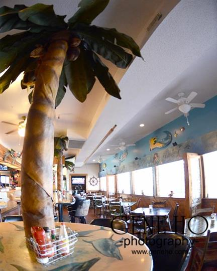 Photo of interior of establishment with palm trees and painting of the sea on the wall