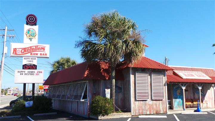 Photo of the exterior of the establishment with palm tree and shrubbery