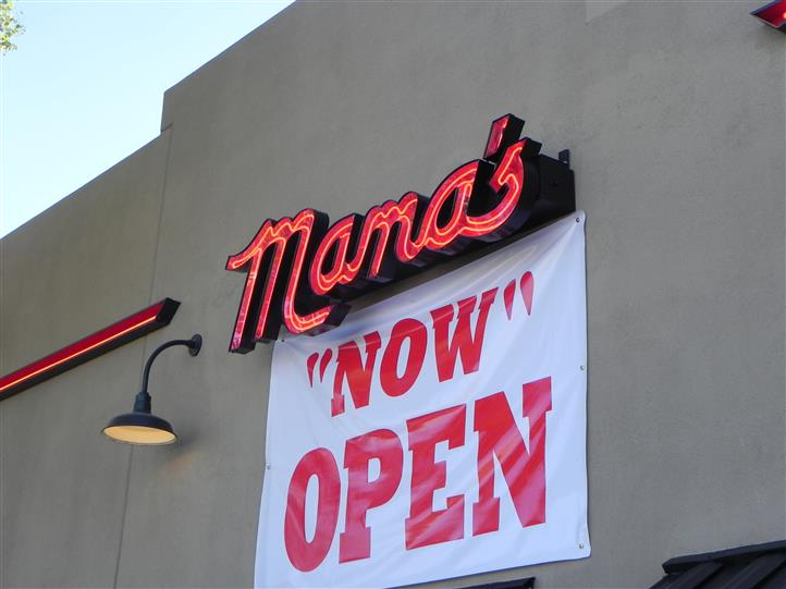 "exterior side of mamas cafe showcasing logo and a ""now open"" sign"