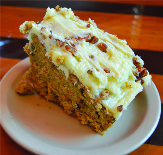 slice of a large carrot cake with icing on a plate