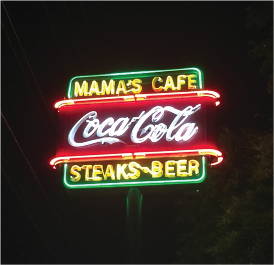 mamas cafe neon sign near the street with coca-cola logo