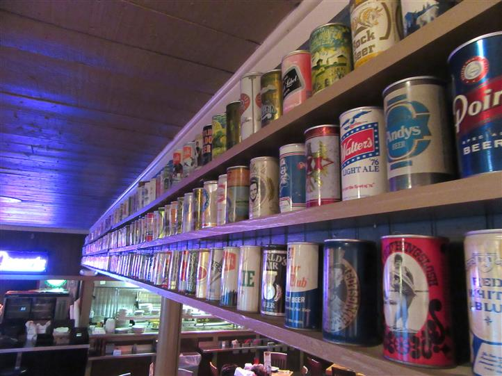 wall of vintage beer cans being displayed inside the restaurant