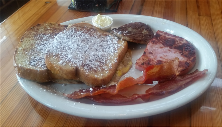 french toast with powered sugar and a side of bacon and ham