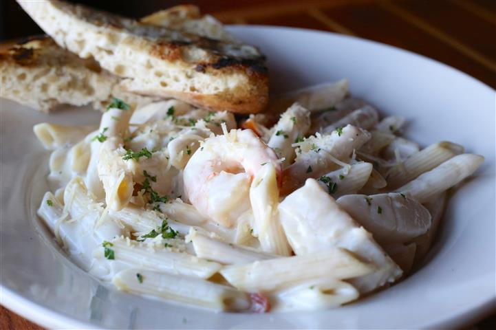 Seafood Alfredo - Shrimp, scallops & snow crab meat with cherry tomatoes over penne pasta in our house-made alfredo sauce