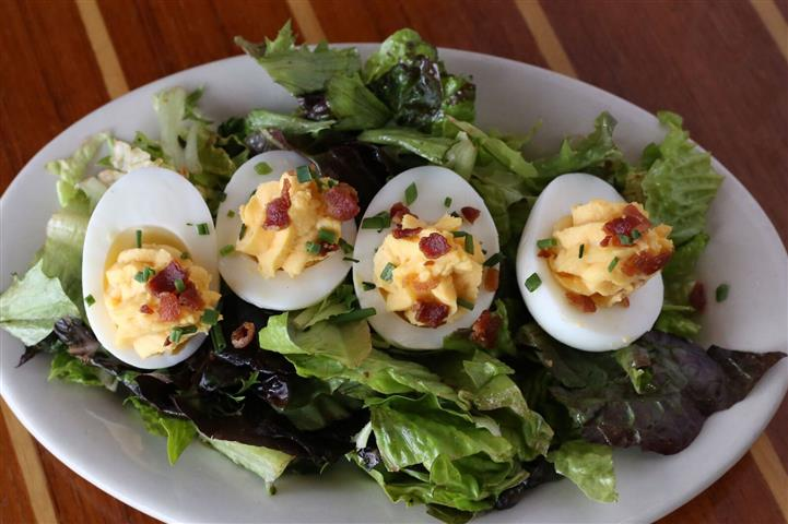 Pimento'd Deviled Eggs - Topped with bacon crumbles & fresh chives served over a small bed of mixed greens tossed in a blood orange vinaigrette