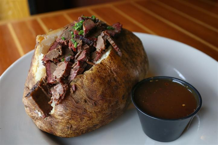 Brisket Potato - Jumbo potato stuffed with cheddar cheese, sour cream & fresh chives then topped with our house smoked Certified Angus Beef® brisket & house-made BBQ sauce