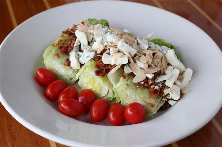Wedge salad - Crispy roma lettuce with gorganzola crumbles, cherry tomatoes, bacon & toasted almonds