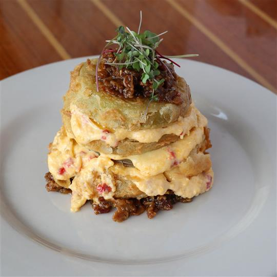 Tomato Stack - Fried green tomatoes layered with pimento cheese then finished with a housemade jalapeno bacon jam