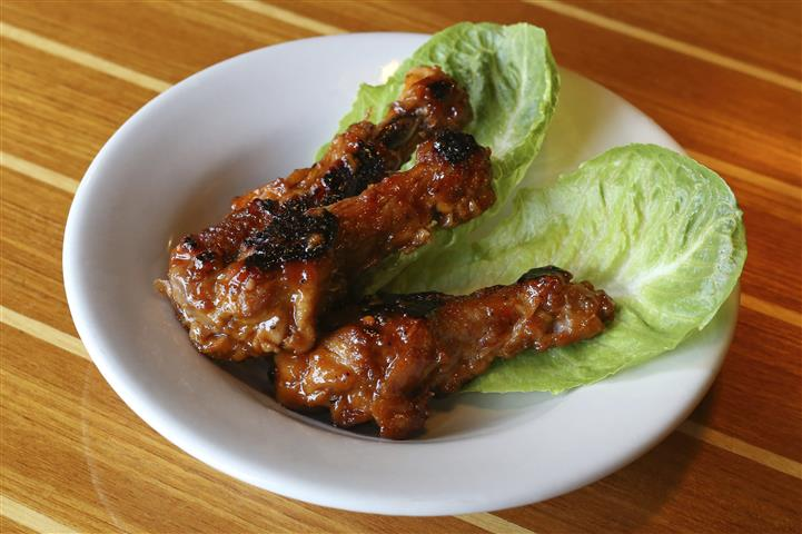 Three drumstick wings in a dark sauce on two romaine lettuce leaves