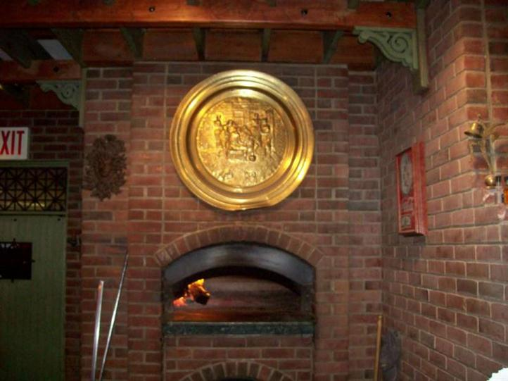 round gold plaque hanging above fireplace