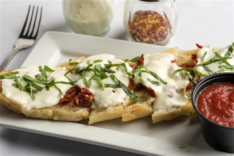 Italian Starter Appetizer. Ciabatta bread with garlic butter, fresh basil, buffalo mozzarella and sun dried tomatoes baked to perfection, served with fresh house tomato sauce.