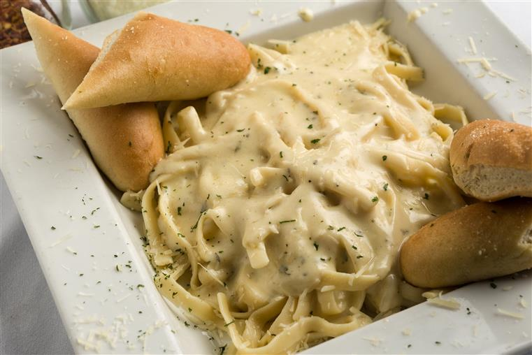 Fettuccine alfredo with breadsticks in white dish