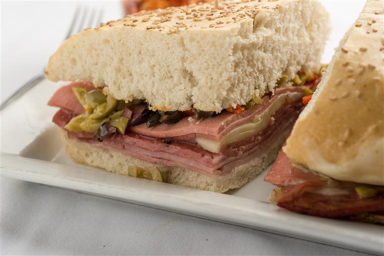 Muffuletta sandwiches on white dish