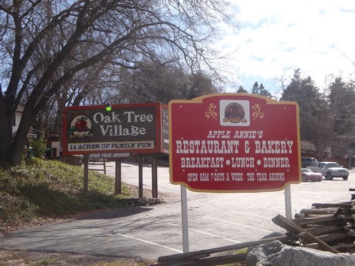 outsde signage for both the oak tree village and apple annies near an open parking lot
