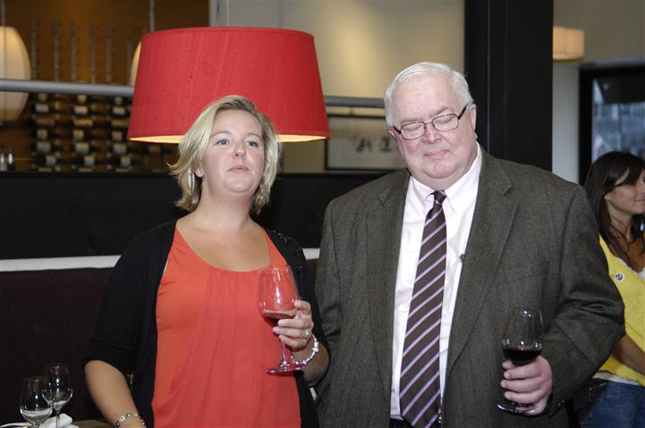 man and woman standing holding glasses of red wine