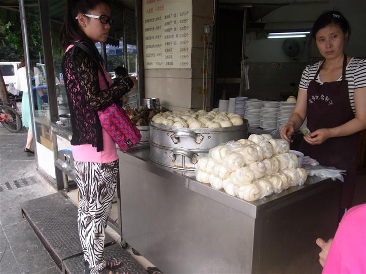 two woman at a booth, one selling food items and one purchasing
