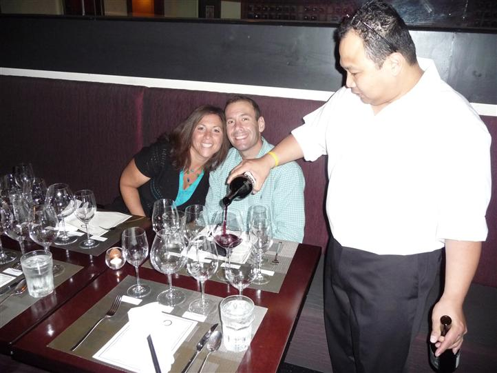 man and woman sitting at table with employee pouring red wine into a glass