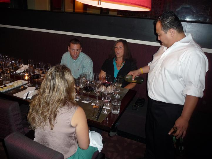 several people sitting at a table with employee pouring wine into a wine glass