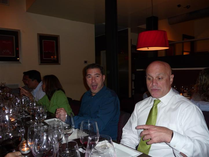 two men sitting at a table, one looking at the camera with his mouth open