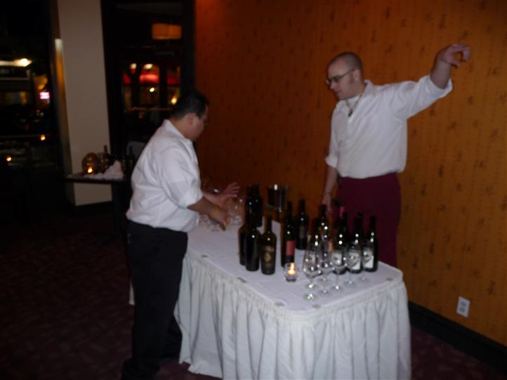 two employees standing at table with bottles of wine