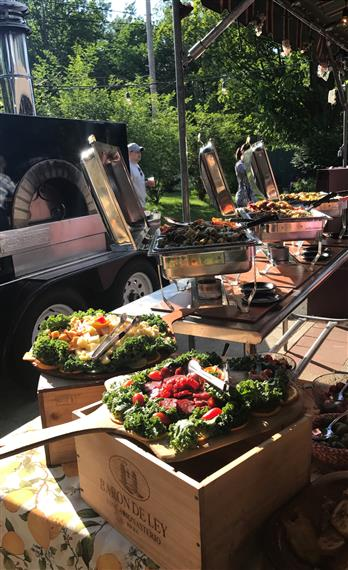 catering spreads on paddles on wood crates outdoors