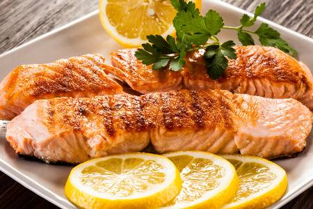 Two grilled salmon filets with sliced lemon on the side and garnished with herb