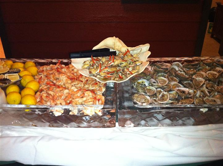 Catering display with a large plate of shrimp cocktail and a large plate of oysters side by side