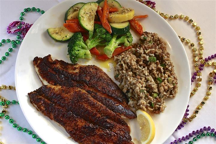 Two broiled filet of fish, a side of mixed rice topped with spring onion, and a side of mixed vegetables