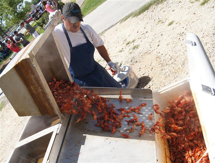 Photo of an employee dumping out a steamer of crawfish