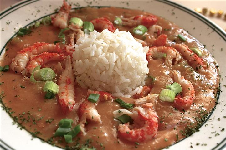 A bowl of seafood gumbo with a scop of white rice in the center