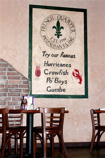 "Interior of resturant with a few tables and chairs and a sign on the wall that says ""try our famous hurricanes, crawfish, po' boys and gumbo"""