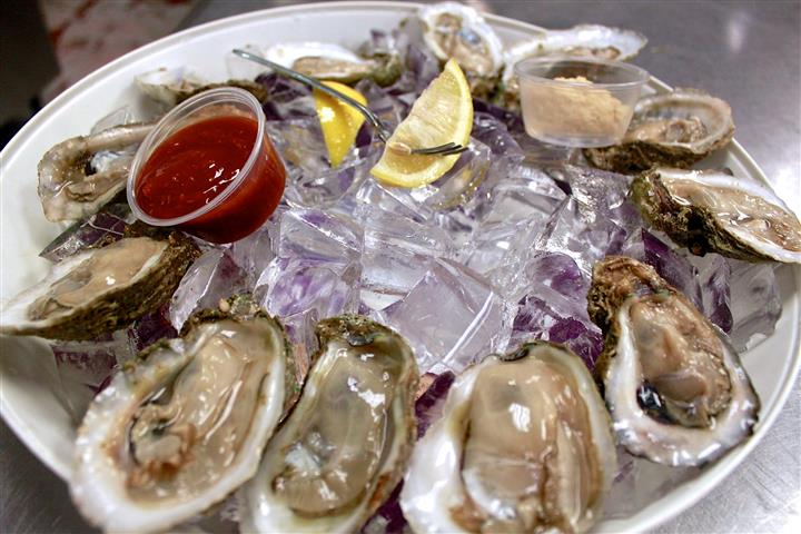 oysters on ice with cocktail sauce and lemon