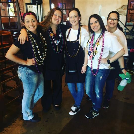 staff wearing mardi gras beads