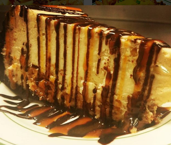 Slice of cheesecake topped with a drizzled of chocolate and caramel