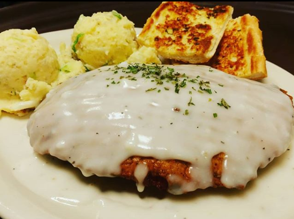 Fried filet of seafood topped with a cream sauce and a green garnish, served with a slide of mashed potatoes and sliced loaf of bread