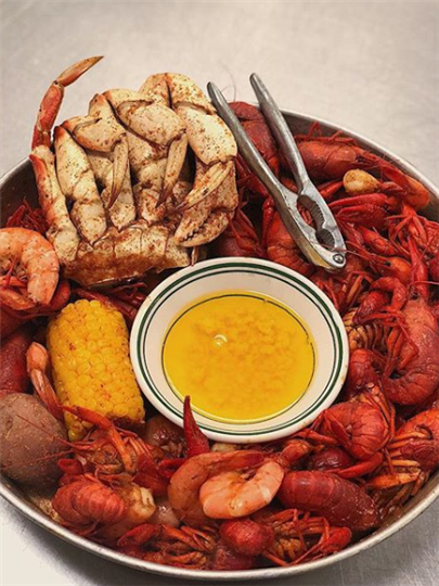 seafood boil with a piece of corn on the cob and a bowl of melted butter