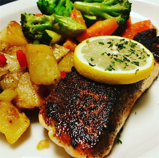 charred fish topped with a slice of lemon, mixed vegetables and home fries.