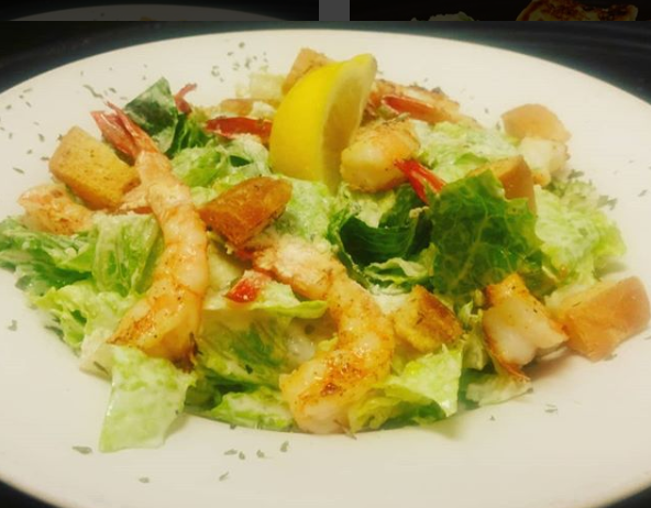 A lettuce salad topped with shrimp and a lemon wedge