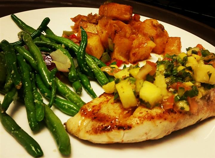Grilled chicken topped with a mango salsa, green beans, and homefries