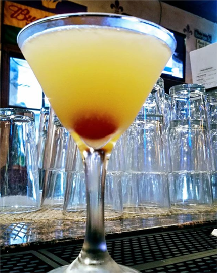 Yellow martini with a cherry in a martini glass on a bar top