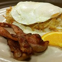 bacon, eggs, and homefries with a slice of orange
