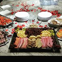 A table arranged with a few catering platters, plates and napkins