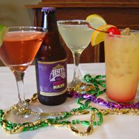 Alcoholic beverages including martinis, a mixed drink, a bottle of beer, on a table decorated with mardi gras decorations
