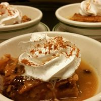 Apple pie in a bowl topped with whip cream and cinnamon