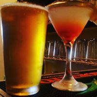 A glass of beer and a colorful martini garnished with a slice of fruit